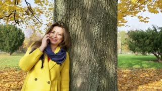 Woman leaning on tree in the autumnal park and talking on cellphone