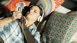 Woman listening music and smiling to the camera while lying on pillows
