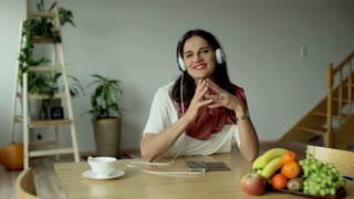 Woman listening music on headphones and smiling to the camera