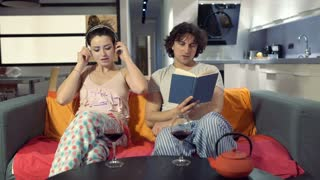Woman listening music on headphones while her boyfriend reading a book