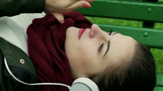 Woman listening music on the bench and warming her hands