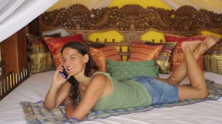 Woman lying on oriental bed and talking on cellphone