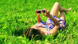 Woman lying on the green meadow and texting on smartphone