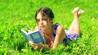 Woman lying on the green meadow and writing notes in the notebook
