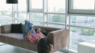 Woman lying on the sofa and browsing internet on cellphone