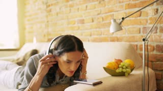 Woman lying on the sofa and listening music on smartphone
