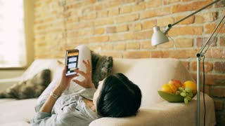 Woman lying on the sofa and texting on smartphone