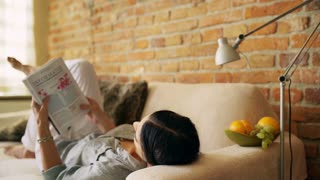 Woman lying on the sofa at home and reading magazine
