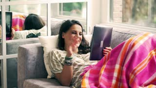 Woman lying under blanket and chatting on tablet on the sofa
