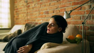 Woman lying under blanket on the sofa