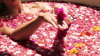 Woman massage her hand by flower in the spa and relaxing