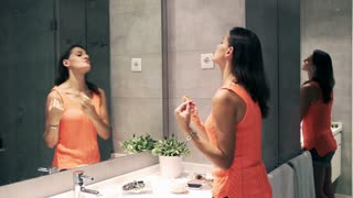 Woman perfume herself in the bathroom and looking at oneself in the mirror
