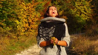 Woman playing with leaves in the autumnal scenery, steadycam shot, slow motion s