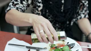Woman pouring olive oil on her meal in the cafe, steadycam shot