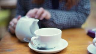 Woman pouring tea from kettle to the cup at wooden table