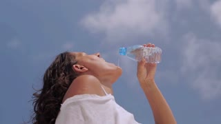 Woman pouring water on her mouth