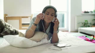 Woman put on headphones and start listening music