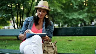 woman reading a book and sitting on a bench in the park