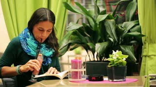 Woman reading book and drinking beverage in restaurant, steadycam shto