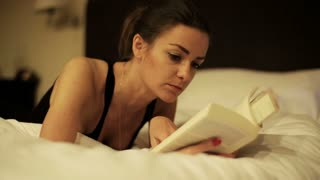Woman reading book and lying on bed, steadycam shot.