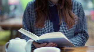 Woman reading book while hot steam going from the cup, steadycam shot