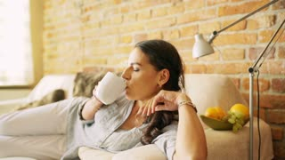Woman relaxing at home and drinking coffee