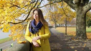 Woman relaxing in the autumnal park and playing with maple leaf