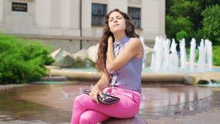 Woman relaxing next to the fountain and bringing out mirror and lipgloss