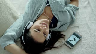Woman relaxing on the bed and listening music on headphones