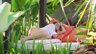 Woman resting in bed in exotic place