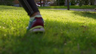 Woman running in park at sunny day, slow motion shot, steadycam shot