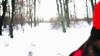 Woman running on the snow in the forest, steady, slow motion shot at 240fps