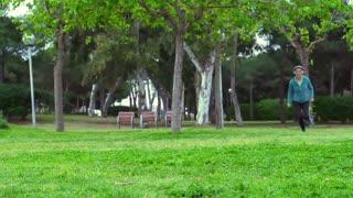 Woman running while listening music, steadycam shot, slow motion shot