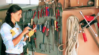 Woman searching tools and using cellphone in the garage