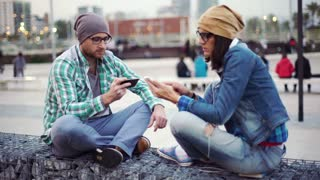 Woman showing something to her boyfriend on smartphone and looking worried