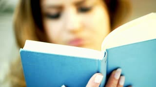 Woman sitting and reading book in blue cover, steadycam shot