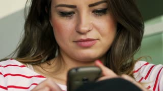 Woman sitting at home and using smartphone