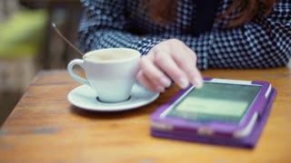 Woman sitting at the table and browsing internet on tablet, steadycam shot
