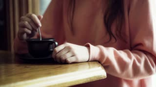 Woman sitting at the table and mixing coffee, closeup
