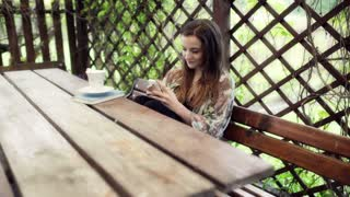 Woman sitting in the arbour and using smartphone