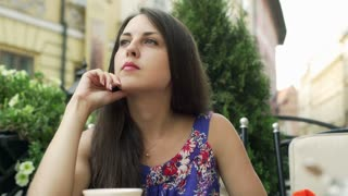 Woman sitting in the outdoor cafe and relaxing, steadycam shot