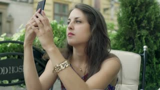 Woman sitting in the outdoor cafe and using smartphone, steadycam shot