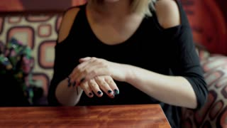 Woman sitting in the restaurant and oil her hands with hand cream
