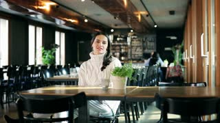Woman sitting in the restaurant and smiling to the camera