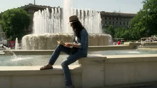 Woman sitting next to the fountain and reading book, steadycam shot