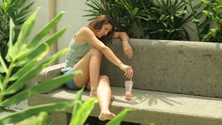 Woman sitting on bench in the garden and crying