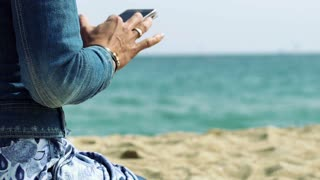Woman sitting on the beach and browsing internet on smartphone, steadycam shot