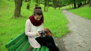 Woman sitting on the bench in park and browsing captured photos on camera