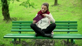 Woman sitting on the bench in park and start listening music
