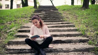 Woman sitting on the stairs in the park and reading book